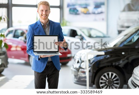 Cheerful car agent holding open laptop and pointing in the empty screen - stock photo