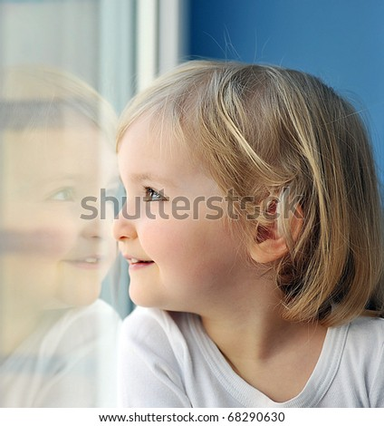 cheerful little girl sits at  window portrait - stock photo
