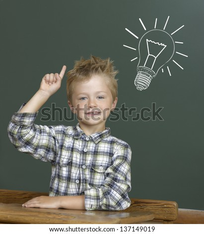 Cheerful smiling child at the blackboard. - stock photo