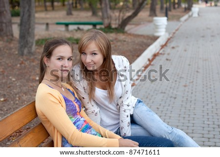 cheerful student girls sitting on the bench - stock photo