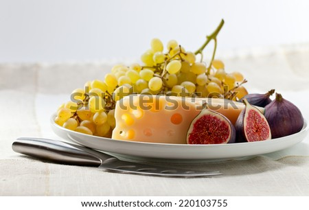 cheese with fruits on a white plate