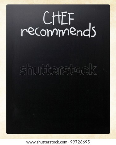 """Chef recommends"" handwritten with white chalk on a blackboard - stock photo"