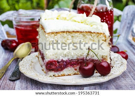Cherry and coconut layer cake on wooden table in the garden  - stock photo