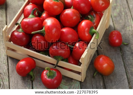 Cherry peppers on wooden background / cherry chili peppers box