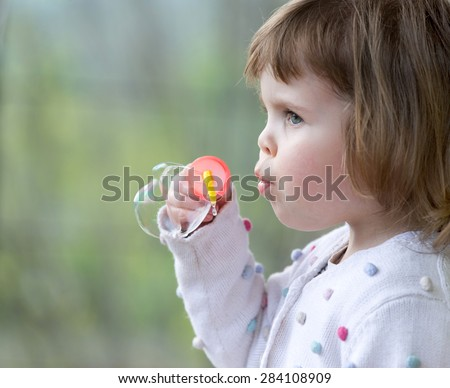 child girl blowing soap bubbles outdoor at sunset - stock photo