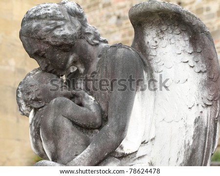 child in angelic arms - antique sculpture on cemetery, Italy, europe - stock photo