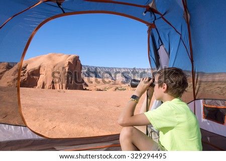 Child looking through binoculars while sitting in a tent. Grand Staircase-Escalante National Monument, Utah