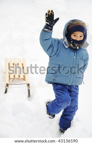 Child playing in the snow with snow - stock photo