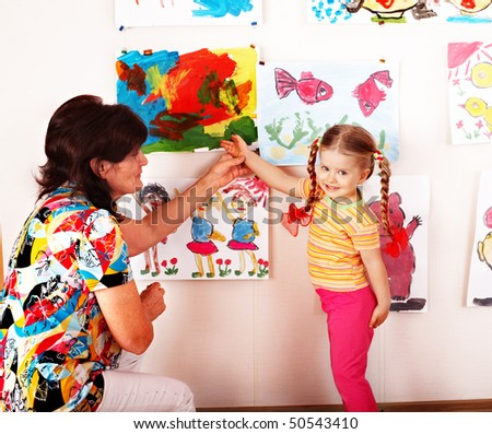 Child preschooler  with teacher draw paints in playroom.Child care. - stock photo