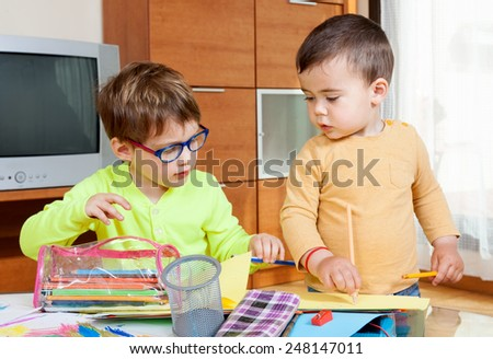 children at  table with crayons and paper. - stock photo