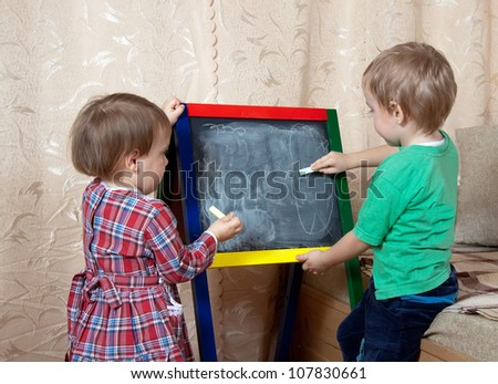 children draws on the blackboard with chalk at home - stock photo