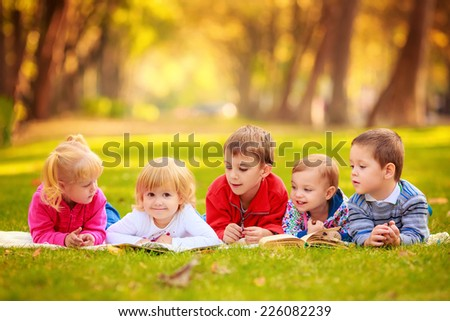 children in nature. reading a book outdoors lying on the grass - stock photo