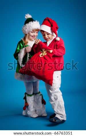 Children in New Year's costumes holding a bag of gifts - stock photo