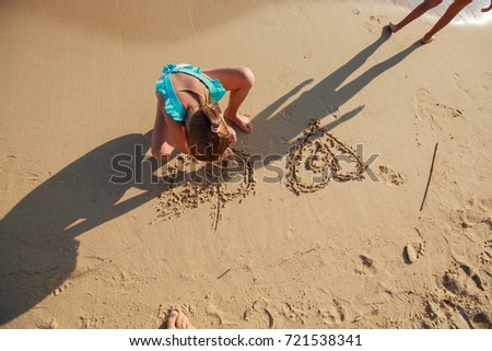 Children playing on the sand beach, little girls drawing heart ,Summer travel vacation.
