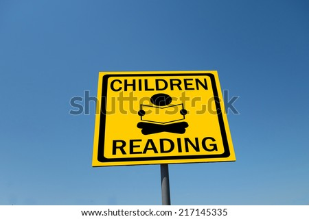 children reading sign with blue sky
