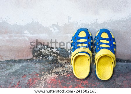 Children's colorful sandals rubber old wall concrete background. - stock photo