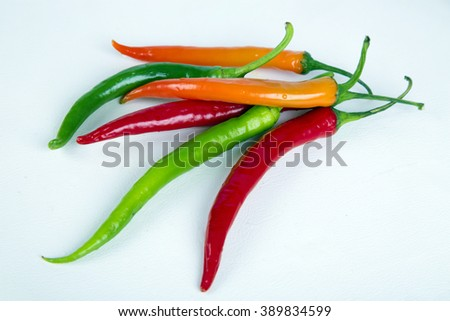 Chili peppers ,red peppers ,orange peppers , green peppers ,vegetables ,fresh vegetables ,spicy ,chilli ,condiments ,vegetables on white ,vegetables in studio ,white background , peppers ,red hot - stock photo