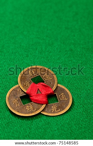 Chinese coins of happiness connected by a red tape on brightly green background - stock photo