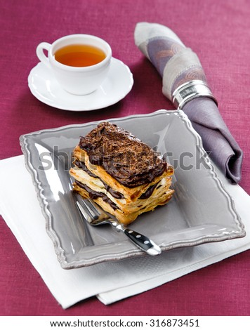 Chocolate millefeuille on a black plate maroon tablecloth with tea in the background - stock photo