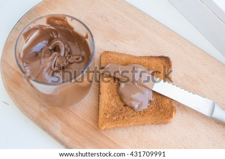 chocolate paste in a jar. Knife and chocolate paste . Chocolate paste crispy toast with banana and strawberries . - stock photo