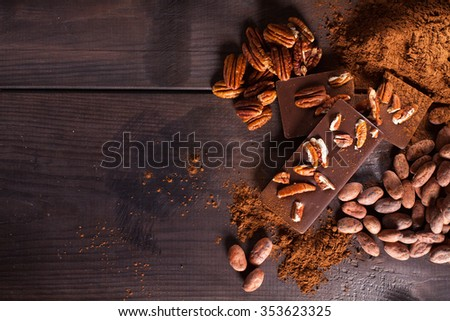 Chocolate products. Chocolate, cocoa beans, cocoa and nuts on wooden background. - stock photo