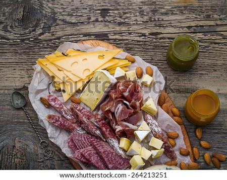 Chopping board with meat selection and cheese, nuts on dark wooden background - stock photo
