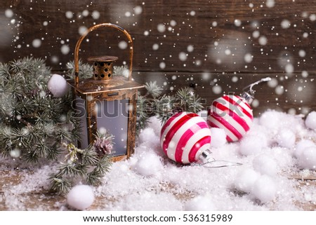Christmas balls, decorative lantern  and branches fur tree on vintage  wooden background.  Selective focus. Place for text. Drawn snow.