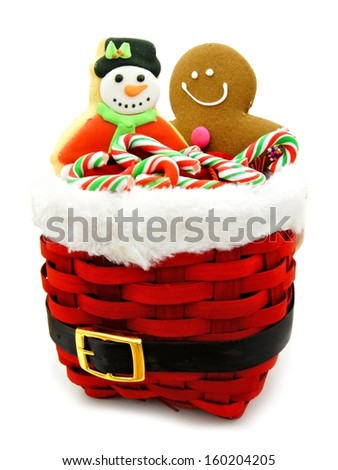 Christmas candy canes and cookies in a Santa basket - stock photo