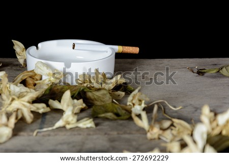Cigarette in ashtray on grunge wood table over black background - stock photo