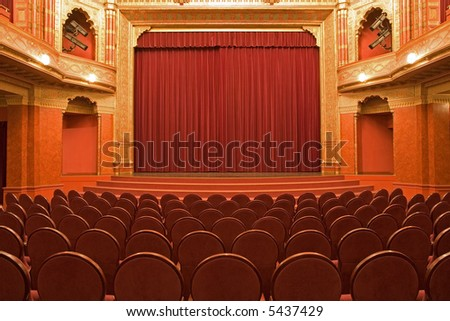 cinema stage with red velvet curtains and  empty chairs in the foreground