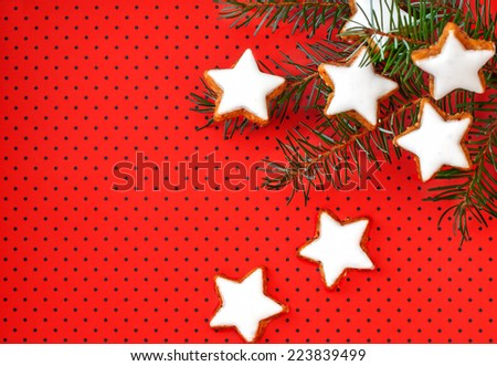 Cinnamon stars on red background with small dots and twig - stock photo