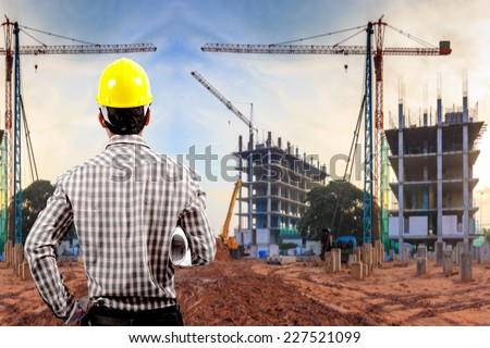 civil engineer working in building construction site against sunset sky with crane construction  - stock photo