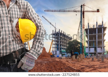 civil engineer working in building construction site and sunset sky with crane construction - stock photo