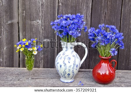 2 clay jugs and drinking glass full of cornflowers, buttercups and daisies placed outside with gray background. Summer still-life - stock photo
