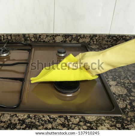 cleaning Stove  in the kitchen with yellow cloth - stock photo
