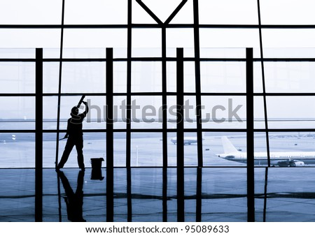cleaning windows at the airport - stock photo
