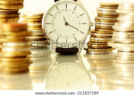 clock and stacks of coins : time - money - stock photo