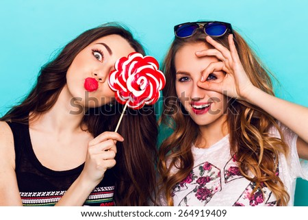 Close op fashion portrait of Two friends have fun , make grimaces ,fun emotions and shows the hand signs.  Pretty girls wearing summer clothes and  posing against blue wall. - stock photo