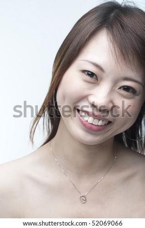 close portrait shot of smiling asian girl - stock photo