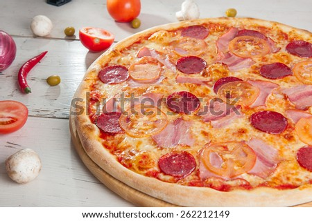 Close up Delicious Meat Pizza with Salami, Bacon and Tomato Slices on a cutting board on white wooden background with different colourful vegetables - stock photo