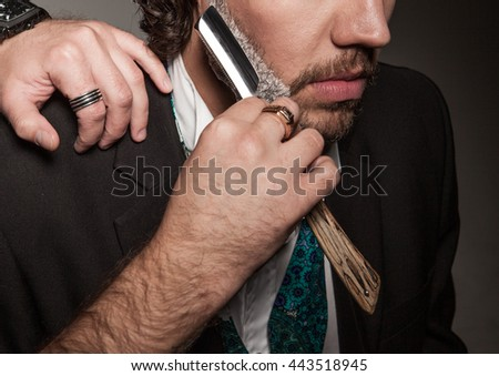 close-up of a man with a beard , Barber shaves with a straight razor beard