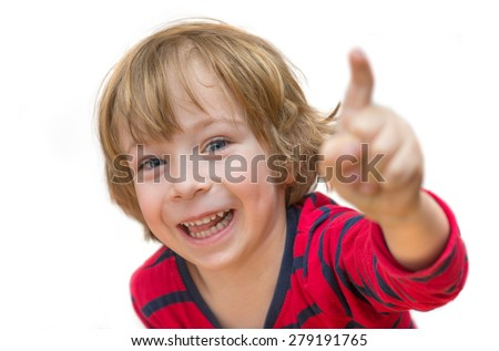 Close up of an adorable little boy in red shirt pointing and smiling isolated on white background