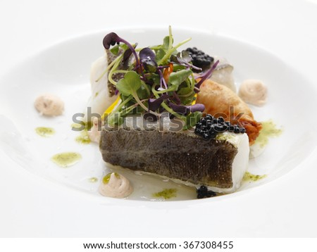 Close up of baked sea bass with vegetables on a dish. Selective focus, shallow DOF - stock photo