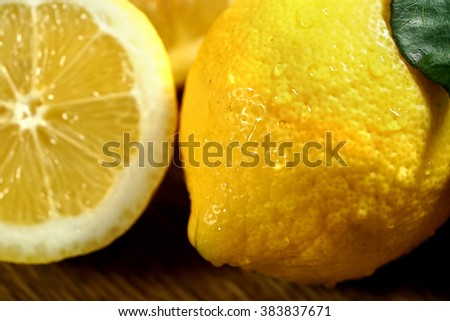 Close up of group of lemons with leaves on wooden boards.