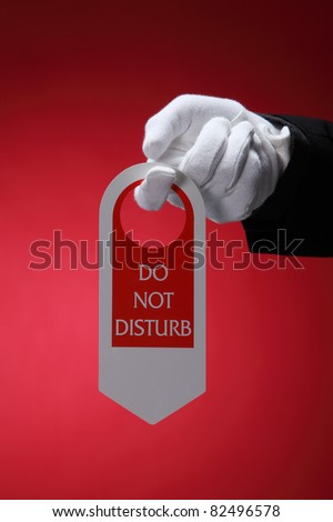 close up of the hotel staff holding a door sign do not disturb - stock photo