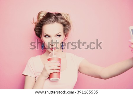 close-up portrait of a beautiful young blonde girl in fashionable sunglasses on a pink background in  studio in a dress  holding a popular phone smiling It makes selfie drink through a straw drink - stock photo