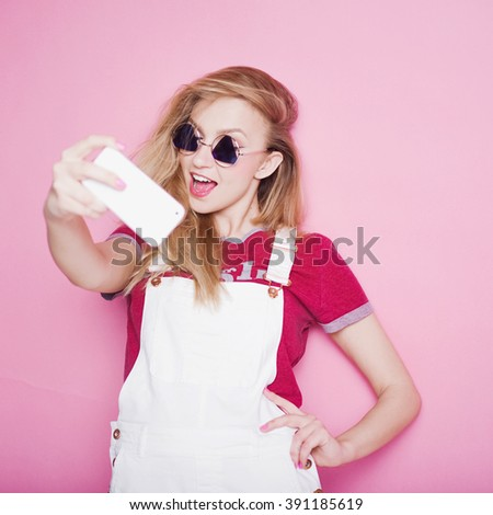 close-up portrait of a beautiful young blonde girl in fashionable sunglasses on a pink background in the studio in white overalls and a T-shirt  holding a popular phone smiling It makes selfie - stock photo