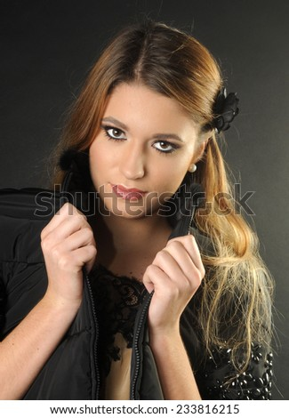 close up portrait of a Young beautiful long haired girl covering herself with a black winter jacket isolated on black background - stock photo