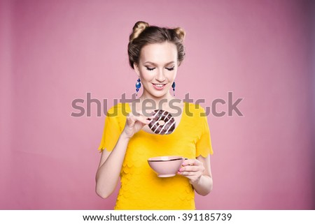 close-up portrait of a young girl hipster slender beautiful blonde bright eat sweet donuts lifestyle posing and smiling on a pink background in yellow blouse - stock photo