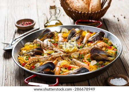 Closeup of paella with seafood on a wooden table, selective focus. - stock photo